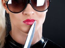 Girl and knife. Woman holding a knife near her red lips Royalty Free Stock Photos