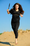 Girl with knife. Girl in black dress with a kukri escapes from dune Royalty Free Stock Photos
