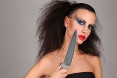 Girl with knife. Close up. Graybackground. Girl with knife, wild girl, high fashion look, perfect make-up, isolated, red lips, dark and mysterious, serious girl Stock Photo