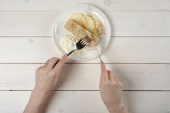 A girl with a knife and fork, cuts a piece of apple strudel with ice cream on white wooden table. A young girl with a knife and fork, cuts a piece of delicious Royalty Free Stock Image