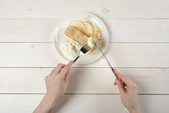 A girl with a knife and fork, cuts a piece of apple strudel with ice cream on white wooden table. A young girl with a knife and fork, cuts a piece of delicious Stock Photos