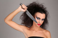Girl with knifeand wild hair. Close up. Graybackground. Girl with knifeand wild hair, high fashion look, perfect make-up, isolated, red lips, dark and mysterious Royalty Free Stock Photography