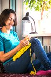 Girl knits crochet at home. Woman engaged in needlework. A knitter sits on a sofa and works. Creative hobby. Training patience and. Perseverance. Crochet thick stock images