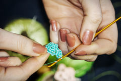 Girl knits a crocheted flower from blue threads against a backgr Royalty Free Stock Image