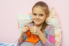 The girl knits on needles orange scarf, smiling looked into the frame. The girl knits on the needles orange scarf, smiling looked into the frame Royalty Free Stock Images