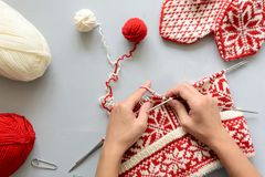 Girl knits red and white Norwegian jacquard hat knitting needles on gray wooden background. Process of knitting. Top view. Flat lay royalty free stock photography