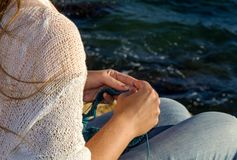 Girl knits on the shores of the Mediterranean Sea. stock photo