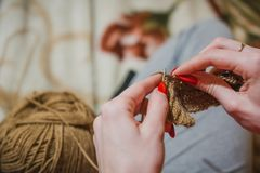 The girl knits spokes. The girl knits a sweater spokes from the shestyankh of threads. A ball of woolen threads and a spoke for knitting Stock Photography