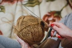 The girl knits spokes. The girl knits a sweater spokes from the shestyankh of threads. A ball of woolen threads and a spoke for knitting Stock Images