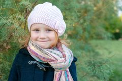 A girl in a knitted beret. Stands on a background of green branches Stock Photos