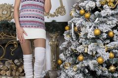 Girl in a knitted dress and white socks is about with Christmas. Trees, Christmas balls ,Golden balls, interior design, log fireplace Royalty Free Stock Images