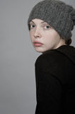 A girl in a knitted hat. Girl in black sweater and knit hat on a gray background. Studio photography Royalty Free Stock Images