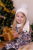 Girl in knitted hat with Christmas golden gift Stock Photography