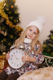 Girl in knitted hat with clock over Christmas tree Stock Image