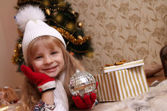 Girl in knitted hat and gloves holding Christmas ball Stock Photos