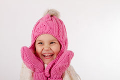Girl in a knitted hat is happy. Smiling laughing girl. Dressed in a pink knitted hat with a pompon and mittens. close-up portrait isolated on white background royalty free stock image