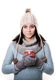 Girl in a knitted hat with a red circle with a coffee in hand is Stock Images