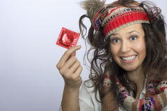 Girl with a knitted hat and a red condom pack in the hand Stock Photo