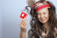 Girl with a knitted hat and a red condom pack in the hand Royalty Free Stock Images