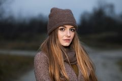 Girl in a knitted hat and scarf freezes in the evening in the autumn on the nature. royalty free stock images