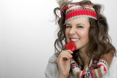 Girl with knitted hat and scarf  holding with teeth a red condom Stock Photography
