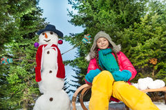 Girl in knitted hat and scarf playing with snowman Stock Photo