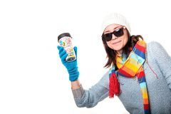 A girl in a knitted hat smiling and holding a thermo coffee on a Royalty Free Stock Images