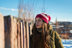 Girl in a knitted hat standing near the fence Royalty Free Stock Photo