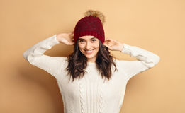 Girl in Knitted Sweater and Beanie Hat over beige background Stock Photos
