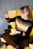 A girl in a knitted sweater holding a coil of colored yarn in his hands, sitting in a yellow chair. A young woman draw a thread royalty free stock photos