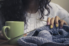 The girl, knitting and green cup Stock Photo