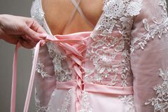 Girl knotted pink dress on a corset. Girl knotted evening pink dress on a corset royalty free stock photo