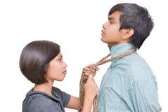Girl knotting necktie of boy Royalty Free Stock Photos