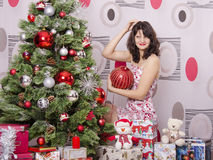 A girl knows where to hang on the Christmas tree big red ball Royalty Free Stock Photography