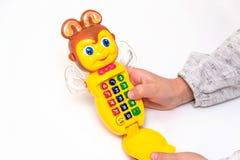 Girl& x27; la mano de s juega en un teléfono colorido del juguete fotografía de archivo libre de regalías