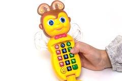 Girl& x27; la mano de s juega en un teléfono colorido del juguete imágenes de archivo libres de regalías