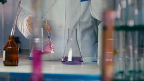 Girl assistant shakes flask with liquid above table closeup