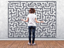 Girl before a labyrinth. Photo of the girl before a wall with a labyrinth Royalty Free Stock Image