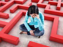 Girl in a labyrinth. Sad girl sits in a labyrinth with red walls Stock Photo