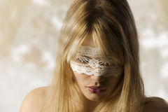 Girl with lace mask. Beautiful blond young woman with a white lace mask looking down royalty free stock photos
