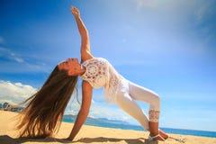 girl in lace wind shakes hair yoga asana arm balance leg cross Royalty Free Stock Photos