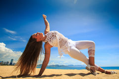 girl in lace wind shakes hair yoga asana arm balance leg cross Stock Image