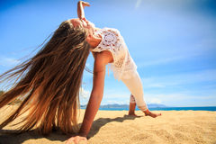 girl in lace in yoga asana arm balance on beach closeup Royalty Free Stock Images