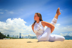 Girl in lace in yoga asana interlaced arms and leg on beach Stock Image
