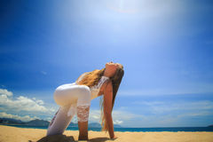 girl in lace in yoga asana revolved side angle on beach Stock Images