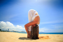 Girl in lace in yoga asana standing forward bend on beach Stock Image