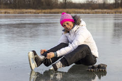 The girl in lace your skates on the ice. Royalty Free Stock Photography