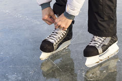 The girl in lace your skates on the ice. Royalty Free Stock Photos