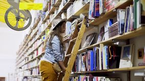 Girl on ladder choosing book in bookshelves. Crop view of young lady on ladder put book on shelf and choosing another in bookstore with decorative bicycle stock video footage
