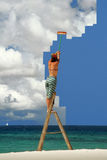 Girl on ladder sweeping sky clean Royalty Free Stock Images